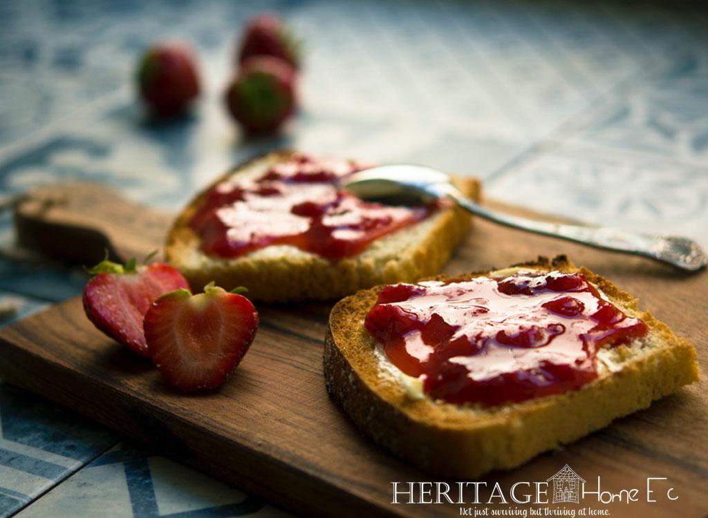 strawberry jam spread on toast set on cutting board